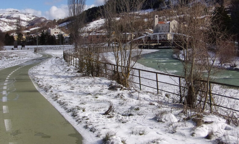 Castel di Sangro the green of the cycle path and the white of the snow on the riverside a unique mountain landscape